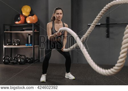 Female Doing Exercises With Heavy Ropes At Gym. Beautiful Young Brunette Having Workout, Wearing Spo