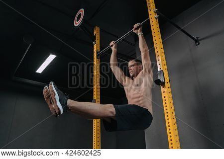 Muscular Brutal Shirtless Athlete Doing Abs Exercises On Horizontal Bar. Practicing Calisthenics At