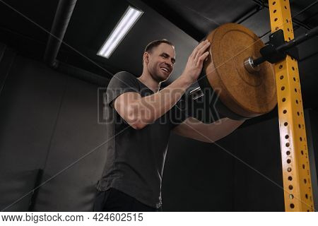 Happy Smiling Athlete Putting On More Weights On Barbell, Prepairing For Weightlifting Training At G