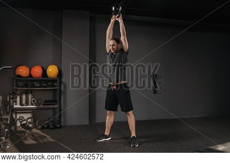 Young Sportsman Doing Kettlebell Swings At Sport Fitness Club. Copyspace. Muscular Strong Man Exerci