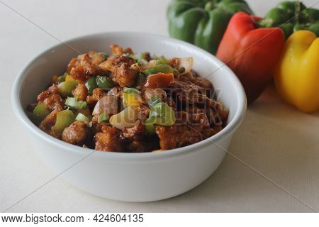Cauliflower Florets Marinated Fried And Sauteed In Sauces With Onions And Bell Peppers. An Indo Chin