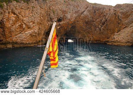 Rocks and flag at the coast Costa Brava Spain