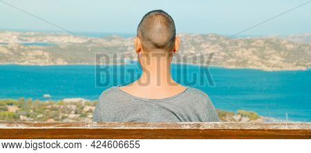 closeup of a young man sitting in a bench in Palau, at the Northern coast of Sardinia, Italy, observes the Mediterranean sea and La Maddalena Archipelago, in a panoramic format to use as web banner
