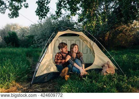 Laughing Young Man And Woman Sitting In A Tent At The Campsite Looking Out. Travelers Relax, Talk An
