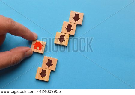 Hand Picked Home Icon With An Arrow Down On Wooden Blocks. The Fall And Crisis Of The Real Estate Ma