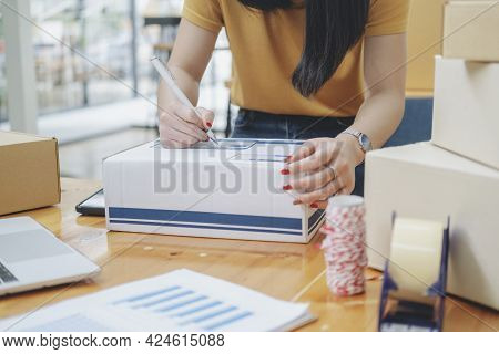 Closeup Hand Of Young Woman Writing Address On Parcel Box  For Delivery Order To Customer, Shipping