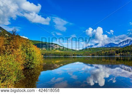 Pyramid Lake. Active eco and photo tourism concept. Rocky Mountains of Canada. Smooth water of the lake reflects Pyramid Mountain  and lush cumulus clouds.