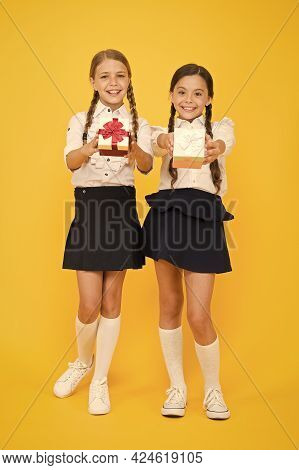 Giving Gifts To The People You Love. Cute Small Children Giving Presents On Yellow Background. Adora