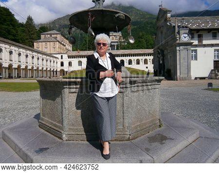 A Seventy Year Old Caucasian Woman Posing Near A Column. High Quality Photo