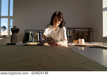 Young Dressmaker Work With Pattern And Fabric. Fashion Design Studio Owner Creating New Collection O