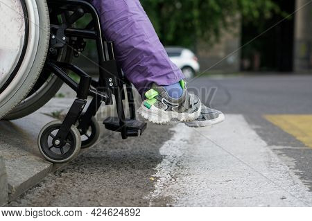 A Girl In A Wheelchair Passes A Dangerous Curb At A Pedestrian Crossing. Risk Of Accident And Crash.