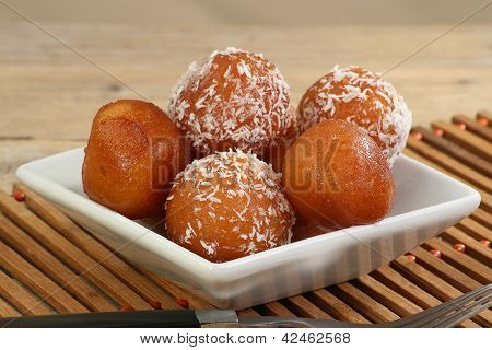 asian gulab jamun on a white dish with coconut poster