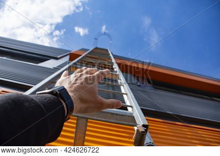 Stairway To Heaven. A Man Reaches Out With His Hand For A Metal Staircase In A Building Against The