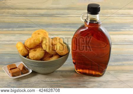 Maple Caramel Corn Puffs Snack In Bowl With Caramel Squares And Bottle Of Maple Syrup