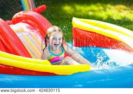 Child In Garden Swimming Pool With Slide
