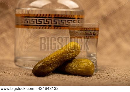 A Glass Decanter With Vodka, A Glass Of Vodka And Pickled Cucumbers On A Background Of Homespun Fabr