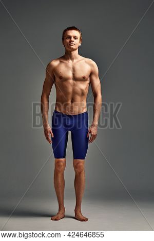 Athlete Swimmer, In Shorts On A Gray Background In Full Growth, Portrait Of An Athlete Swimmer In Th