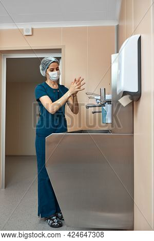 Woman Surgeon, Washes Her Hands In The Preoperative Unit, The Surgeon Disinfects His Hands Before Th