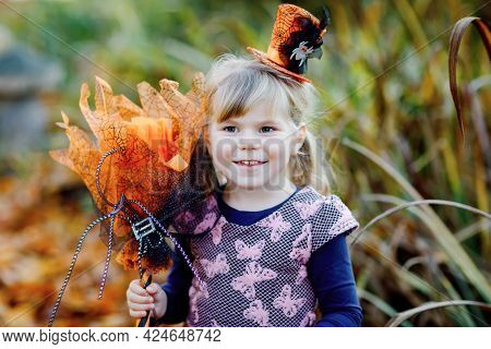 Portrait Of Little Toddler Girl Dressed As A Witch Celebrates Halloween. Happy Child Outdoors, With