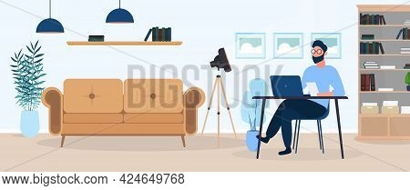 A Guy With Glasses Sits At A Table In His Office. A Man Works On A Laptop. Office, Sofa, Bookshelf,
