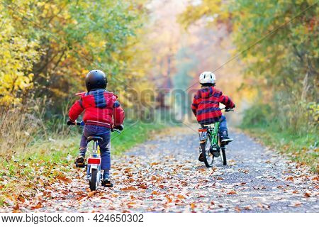 Two Little Kid Boys In Colorful Warm Clothes In Autumn Forest Park Driving Bicycle. Active Children