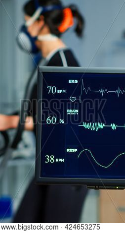 Medical Researcher Examining Ekg Image Showing On Monitor While Patinet With Mask Running On Cross T