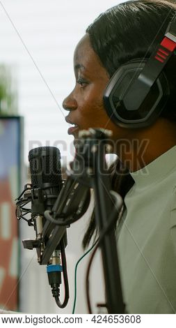 African Gamer Checking Sound Mixer Sitting In Gaming Room And Talking Into Microphone For Space Shoo