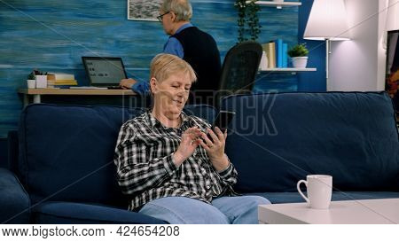 Happy Middle Aged Mature Woman Enjoying Using Mobile Apps Texting Typing Messages Sit On Sofa, Smili