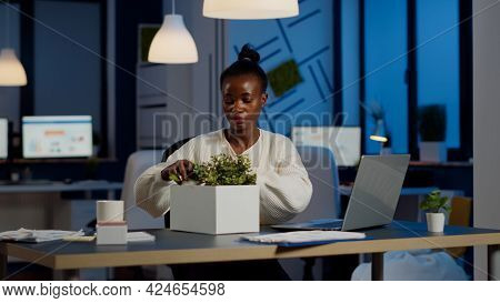 Sad African Fired Businesswoman Packing Things In Box Being Dismissed From Job Late At Night. Overwo