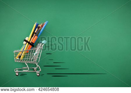 Concept Buying School Supplies With Tools On Trolley Sliding On A Green Table. Top View. Horizontal