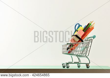 School Supplies Shopping Concept With Mini Shopping Cart Full Of School Supplies On Green Table With