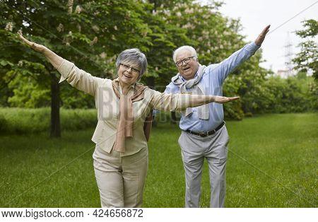 Portrait Of Happy Retired Senior Couple Having Fun In Green Summer Park Or Garden
