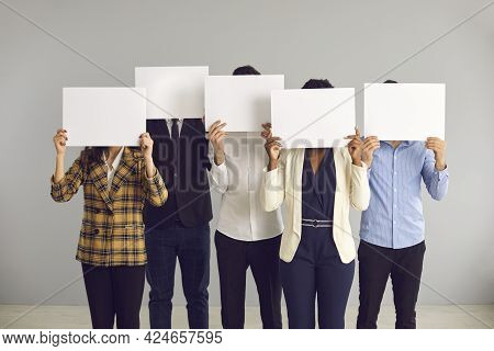 Group Of Anonymous People Covering Faces Hiding Behind White Mockup Sheets Of Paper