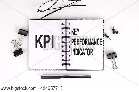 Notebook With Kpi On Table With Office Tools