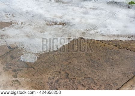 A Pile Of Snow Melting On Walkway During Warm Winter. Grungy Melting Snow On An Asphalt Surface. End