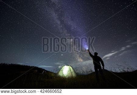 Back View Of Male Traveler Illuminating Beautiful Starry Sky. Man Hiker Shining Flashlight Into Nigh