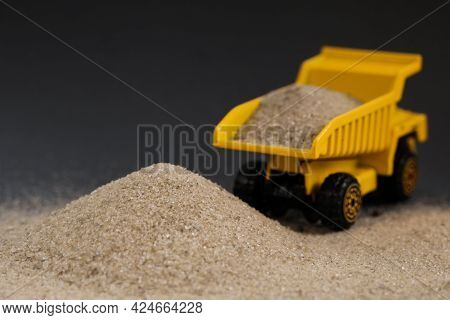 Yellow Dump Truck On Dark Grey Background. Bulk Load Materials, Sand, Bricks, Chippings, Cement Deli