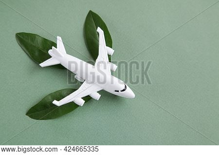 White Airplane Model Emitting Fresh Green Leaves On Green Background. Sustainable Travel, Clean And
