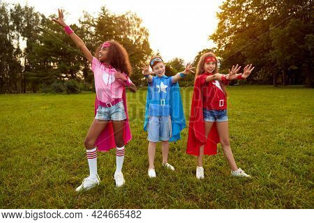 Full Body Of Happy Multiracial Kids In Colorful Superhero Cloaks Outstretching Hands Ready To Help W