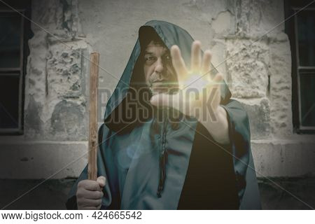 Radiance And Power Emanates From The Hand Of An Elderly Monk In A Black Cassock.concept: Healing And