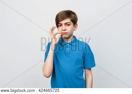 Shh Its Secret. Portrait Of Serious Boy 12-14 Years Old Showing Zip Gesture As If Shutting Mouth On