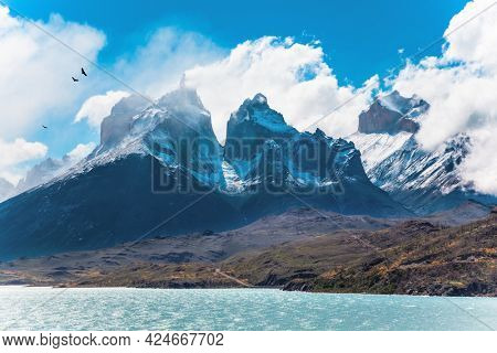 Travel to Chile. Picturesque lake Pehoe in the Patagonian Andes. The famous snow-capped cliffs of Los Cuernos by the lake. The lake with bright azure water from melting glaciers.
