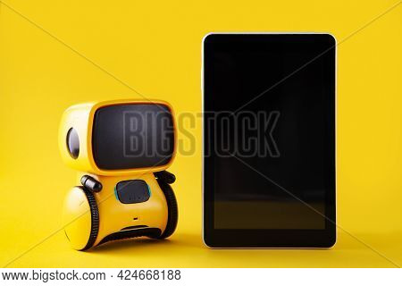 Robot Toy And Smart Phone On Yellow Backround. Chatbot Concept. Copy Space