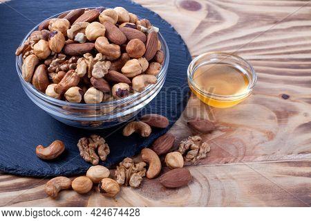 Assorted Nuts In Glass Bowl With Honey Bowl. Mixed Nuts On Wooden Table. Black Stone Plate On Wooden