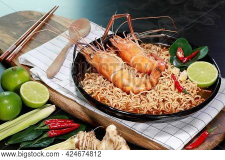 Spicy Instant Noodles Soup With Rivers Shrimp On Top, On Black Table Background With Smoke. Tom Yum