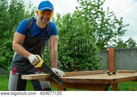 Male Carpenter With A Saw With Protective Tools Sawing Hand Saw Wood