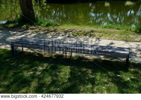 Dusty Park Path Along The Pond Winding Through A Meadow. It Leads To The Bridge And The Share Of The