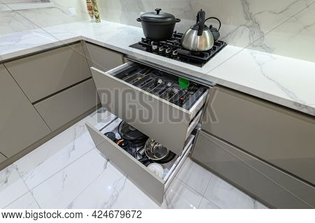 Closeup high angle inside view to open drawers with cutlery and cooking utensils at modern grey woden kitchen in classic style