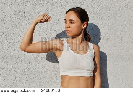 Portrait Of Dark Haired Athletic Woman Wearing White Top Showing Biceps And Looking Away, Posing Out