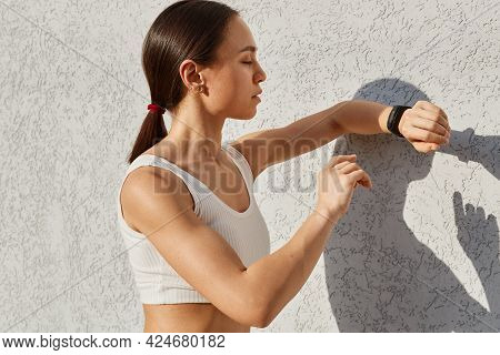 Sporty Woman With Dark Hair Posing Near Gray Wall Outdoor And Looking At Fitness Bend On Her Hand, W